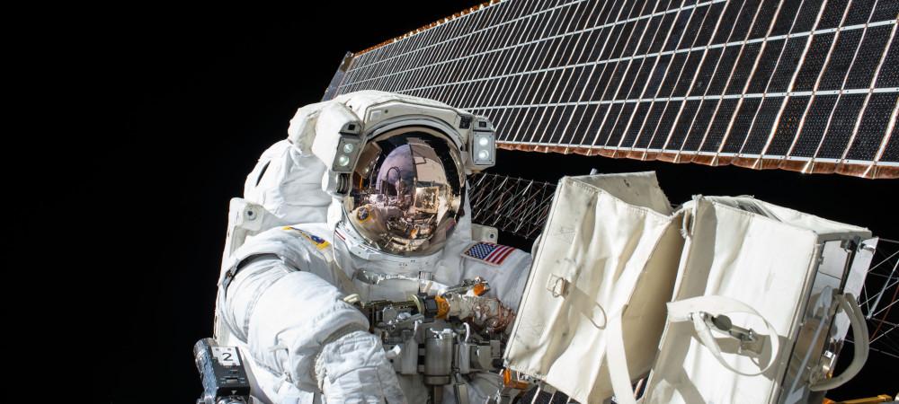 Astronaut neben Raumstation mit Solarzellen
