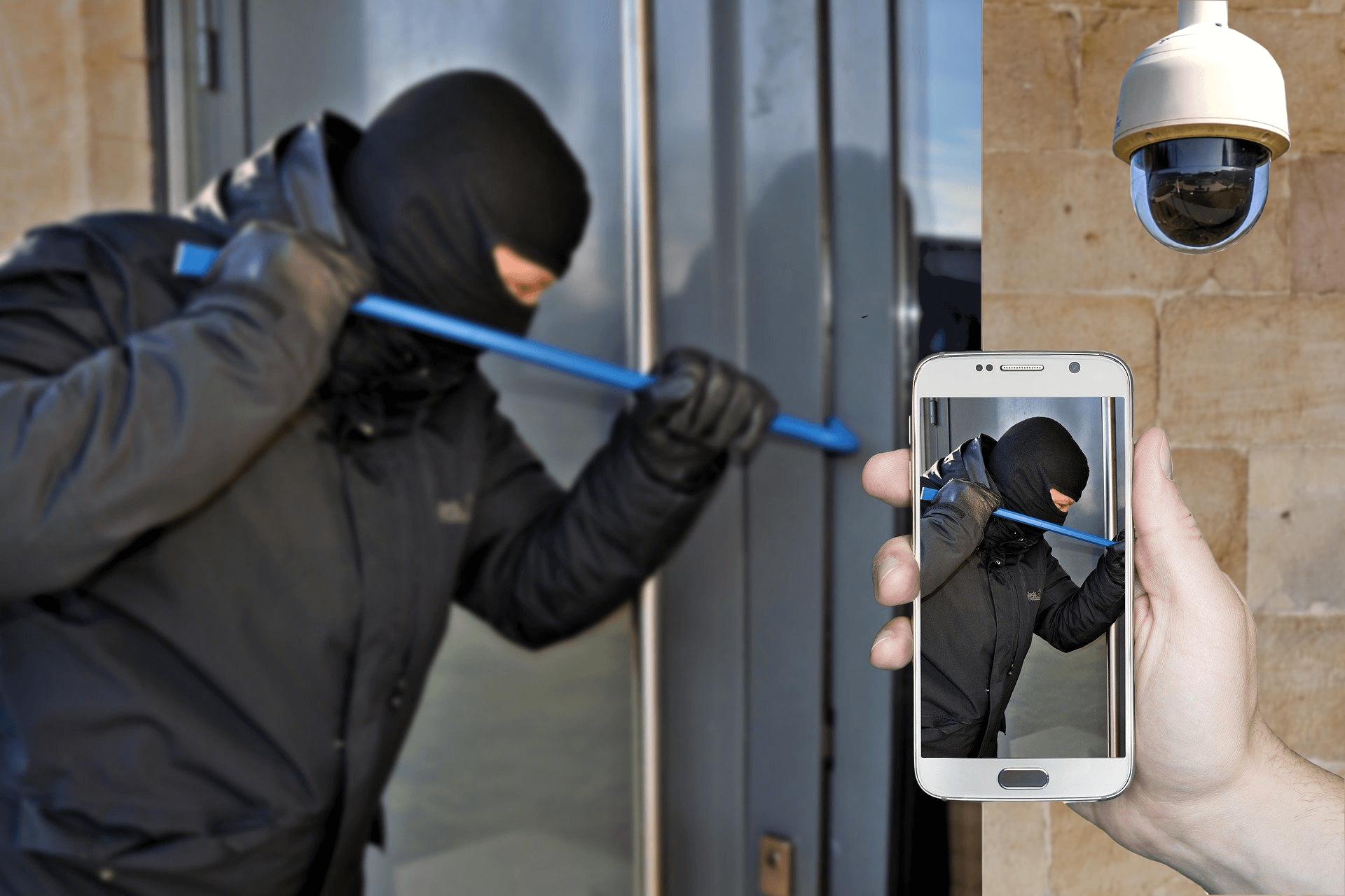 Einbrecher neben Alarmanlage und Smartphone