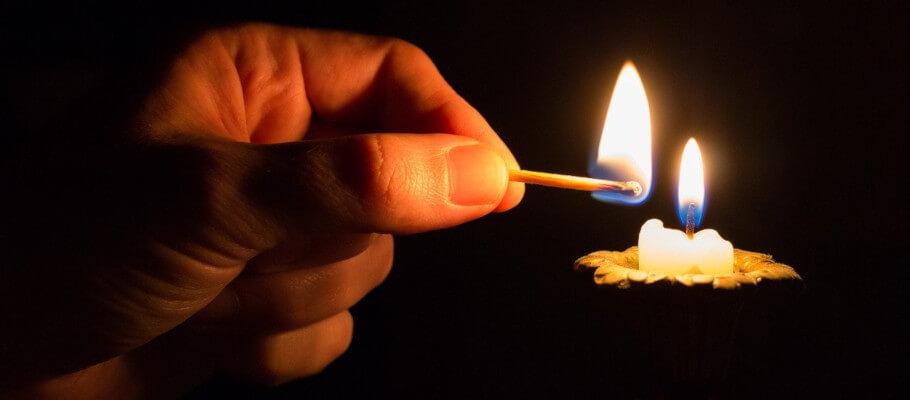 Mensch zündet Kerze an